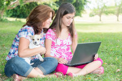Hispanic girl and her mother browsing the web outdoors Stock Photos