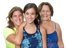 Hispanic girl with her mother and grandmother hugging and smiling. Isolated on white Royalty Free Stock Photo