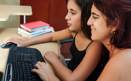 Hispanic girl and her mother using a computer Stock Photography