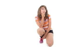 Hispanic girl kneeling with hand on her chin Stock Photo