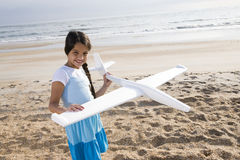 Hispanic girl playing with toy plane on beach Stock Photo