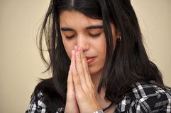 Hispanic girl praying at home. A brunette Latin teenager prays with reverence and faith. Hispanic young woman praising God in her daily devotional Stock Photography