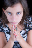 Hispanic girl praying with a crucifix Stock Photos