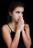 Hispanic girl praying isolated on black Royalty Free Stock Photo