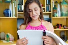 Hispanic girl reading at home Stock Image