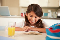 Hispanic Girl Reading Homework At Table Stock Photo