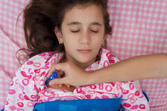 Hispanic girl sick with fever laying in bed Royalty Free Stock Image