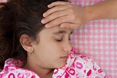Hispanic girl sick with fever laying in bed Stock Photography