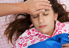 Hispanic girl sick with fever laying in her bed Royalty Free Stock Images