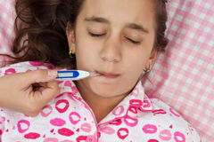 Hispanic girl sick with fever laying in her bed Royalty Free Stock Photo