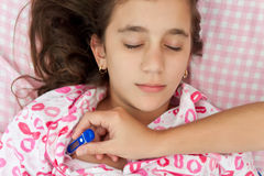 Hispanic girl sick with fever laying in her bed Stock Images