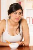 Hispanic girl sitting with cereal bowl Stock Photo