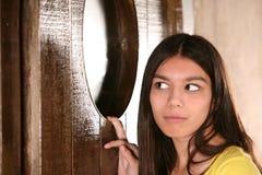 Hispanic girl sneeking a look in window Royalty Free Stock Photo