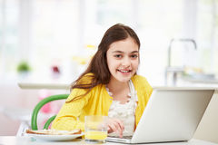 Hispanic Girl Using Laptop Eating Breakfast Royalty Free Stock Images