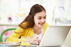 Hispanic Girl Using Laptop Eating Breakfast Stock Photos