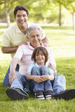 Hispanic Grandfather, Father And Son Relaxing In Park Stock Image