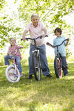Hispanic Grandfather With Grandchildren In Park Riding Bikes Stock Photo