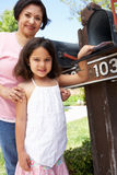 Hispanic Grandmother And Granddaughter Checking Mailbox Stock Photos