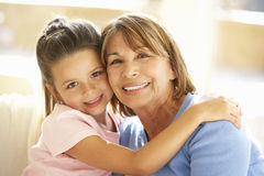 Hispanic Grandmother And Granddaughter Relaxing At Home Stock Photo