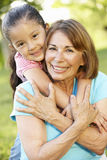 Hispanic Grandmother And Granddaughter Relaxing In Park Stock Image