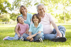 Hispanic Grandmother And Grandfather Relaxing With Grandchildren In Park Royalty Free Stock Image