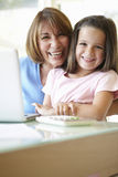 Hispanic Grandmother Using Laptop And Calculator With Granddaugh Stock Images