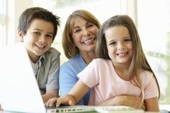 Hispanic Grandmother Using Laptop With Grandchildren Stock Photos
