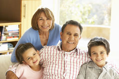 Hispanic Grandparents With Grandchildren Relaxing On Sofa At Hom Stock Photo