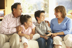 Hispanic Grandparents With Grandchildren Relaxing On Sofa At Home Stock Images