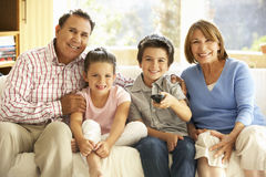 Hispanic Grandparents With Grandchildren Watching TV On Sofa At Stock Photos