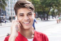 Hispanic guy in the city flirting at phone Stock Photo