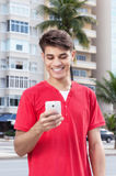 Hispanic guy in the city typing message at phone Royalty Free Stock Photos