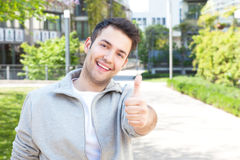 Hispanic guy in a grey jacket showing thumb up outside. Hispanic guy in a grey jacket showing thumb outside on campus with buildings, trees and meadow in the Stock Images