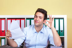 Hispanic guy at office is happy about good news. Young hispanic guy at office with a letter in his hand is happy about the good news Stock Photography