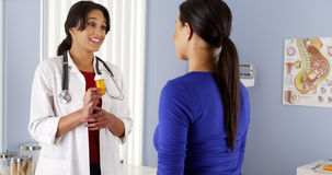 Hispanic gynecologist talking to African Patient about new prescription Stock Image
