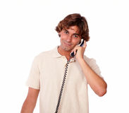 Hispanic handsome man conversing on phone. Portrait of a hispanic handsome man conversing on phone while standing on white background Royalty Free Stock Photos
