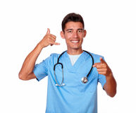 Hispanic handsome nurse gesturing a call with hand Stock Image