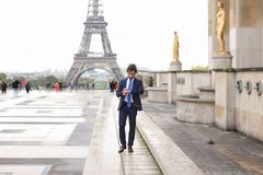 Hispanic journalist close to Eiffel Tower reading newspaper and. Young pressman reading newspaper article near Eiffel Tower and looking at watch. Handsome boy Stock Photo