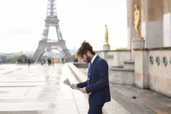 Hispanic journalist close to Eiffel Tower reading newspaper and. Young pressman reading newspaper article near Eiffel Tower and looking at watch. Handsome boy Royalty Free Stock Photography