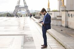 Hispanic journalist close to Eiffel Tower reading newspaper and. Young pressman reading newspaper article near Eiffel Tower and looking at watch. Handsome boy Stock Photography