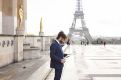 Hispanic journalist close to Eiffel Tower reading newspaper and. Young pressman reading newspaper article near Eiffel Tower and looking at watch. Handsome boy Royalty Free Stock Images