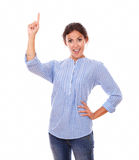 Hispanic lady pointing up while standing Stock Photo