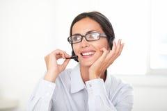 Hispanic lady secretary speaking on her headphones Stock Photos