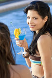 Hispanic Latina Woman Drinking Cocktail By Pool. Stunningly beautiful young Latina Hispanic woman in drinking a cocktail by a blue swimming pool with her friend Stock Photo