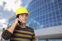 Hispanic Male Contractor on Phone in Front of Building Royalty Free Stock Images