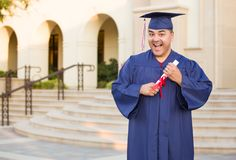 Hispanic Male With Diploma Wearing Graduation Cap and Gown On Campus stock photo