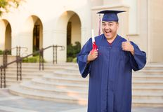 Hispanic Male With Diploma Wearing Graduation Cap and Gown On Campus royalty free stock images