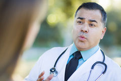 Hispanic Male Doctor or Nurse Talking With a Patient Stock Photos