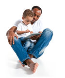 Hispanic male educator and little boy reading fairy tale on touch pad computer Royalty Free Stock Photography