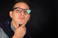 Hispanic male headshot wearing tight shirt. Sweater over shoulders and glasses looking sophisticated facing camera, black background Royalty Free Stock Photo
